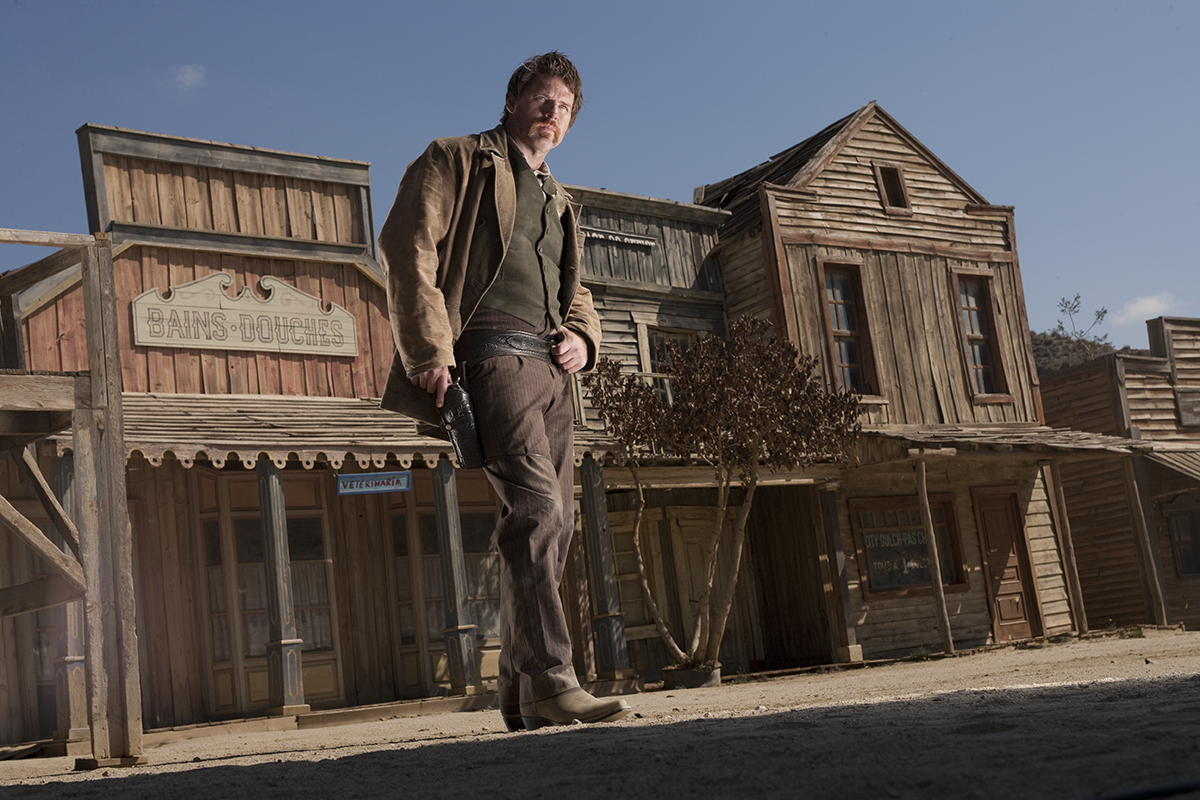 Issac (Ben Browder) standing in street. Episode A Town Called Mercy