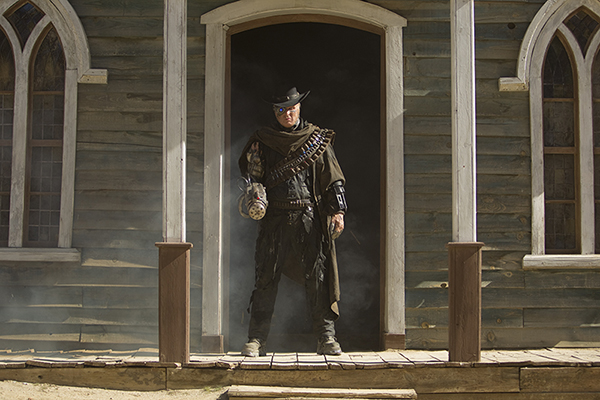 The Gunslinger (Andrew Brooke) stands in doorway of church. Episode A Town Called Mercy