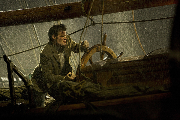 film still from tv series Doctor Who - The Doctor at the wheel of a sailing ship in storm