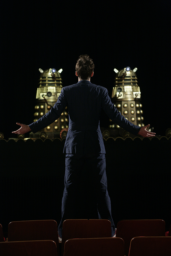 production still photo of The Doctor confronting Daleks in a theatre