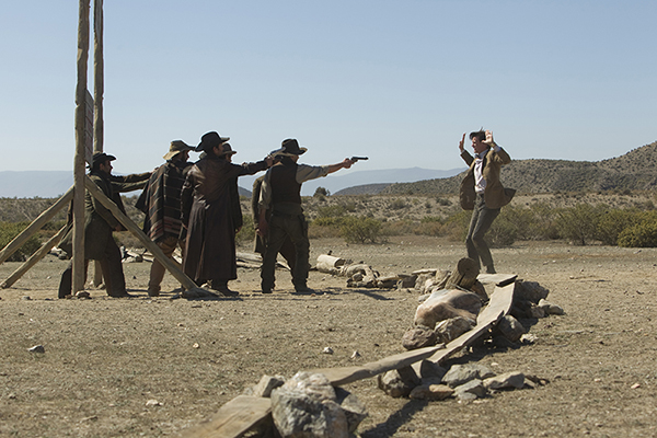 unit still of The Doctor with hands up as crowd of townfolk point guns at him
