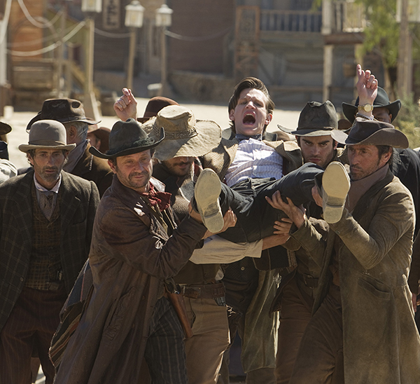 photo of The Doctor being carried on shoulders of townsfolk, running him out of town