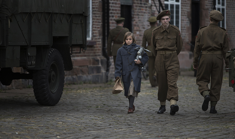 Lotte Koehler (Lucy Ward) walking holding toy, escorted by soldier