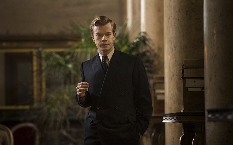Ringwood (Alfie Allen) smoking, waiting in hotel lobby